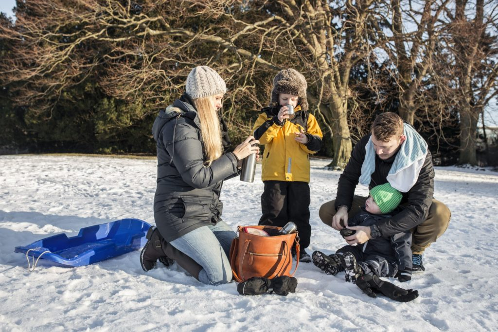 Family having hot chocolate on snow covered field